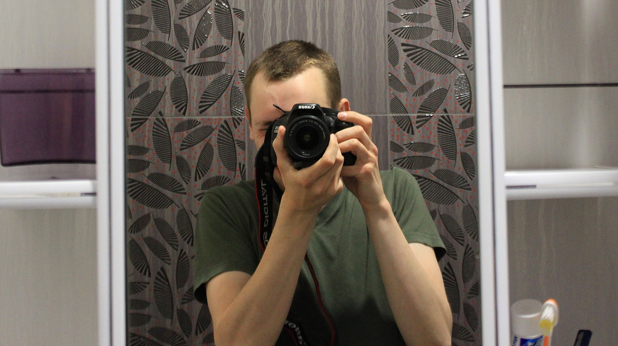 A bathroom mirror selfie with a Canon 600D.