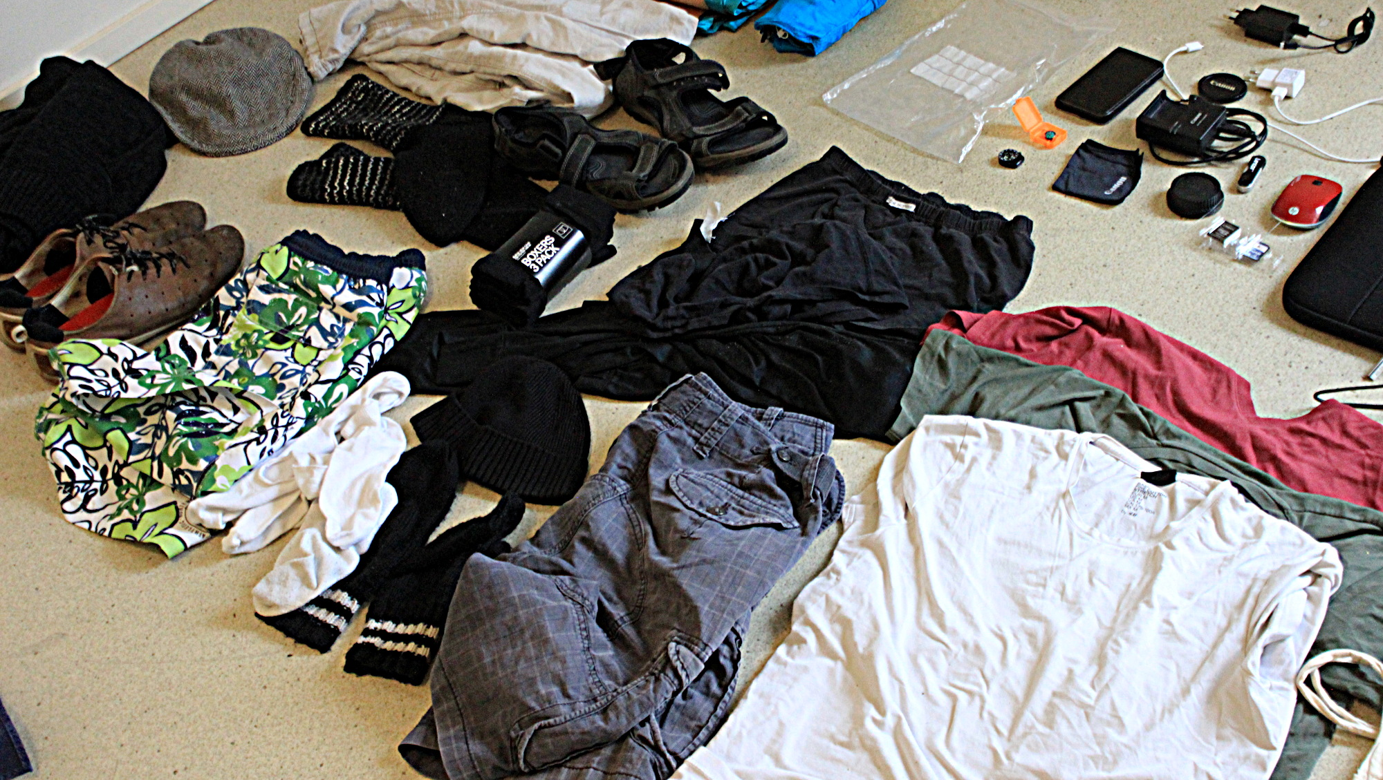 Round the world packing list. Clothes for a trip around the world spread on the floor.
