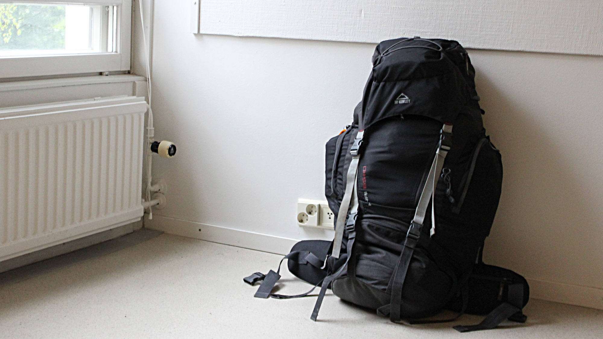 How to go on a trip around the world? Step one is packing. Pictured is a packed black McKinley backpack in an empty apartment.