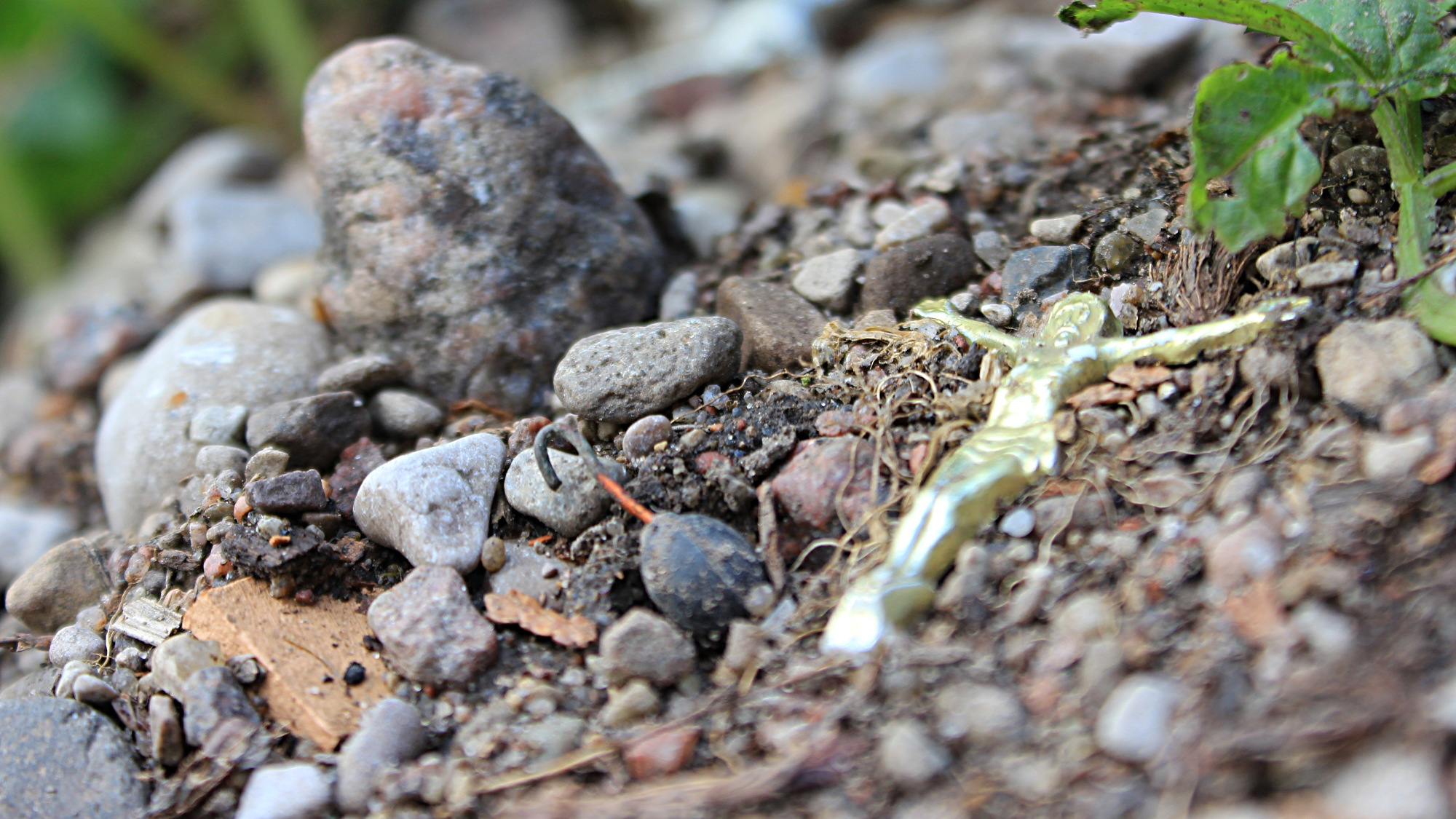 A miniature statue of Jesus lying on the ground beside small rocks.