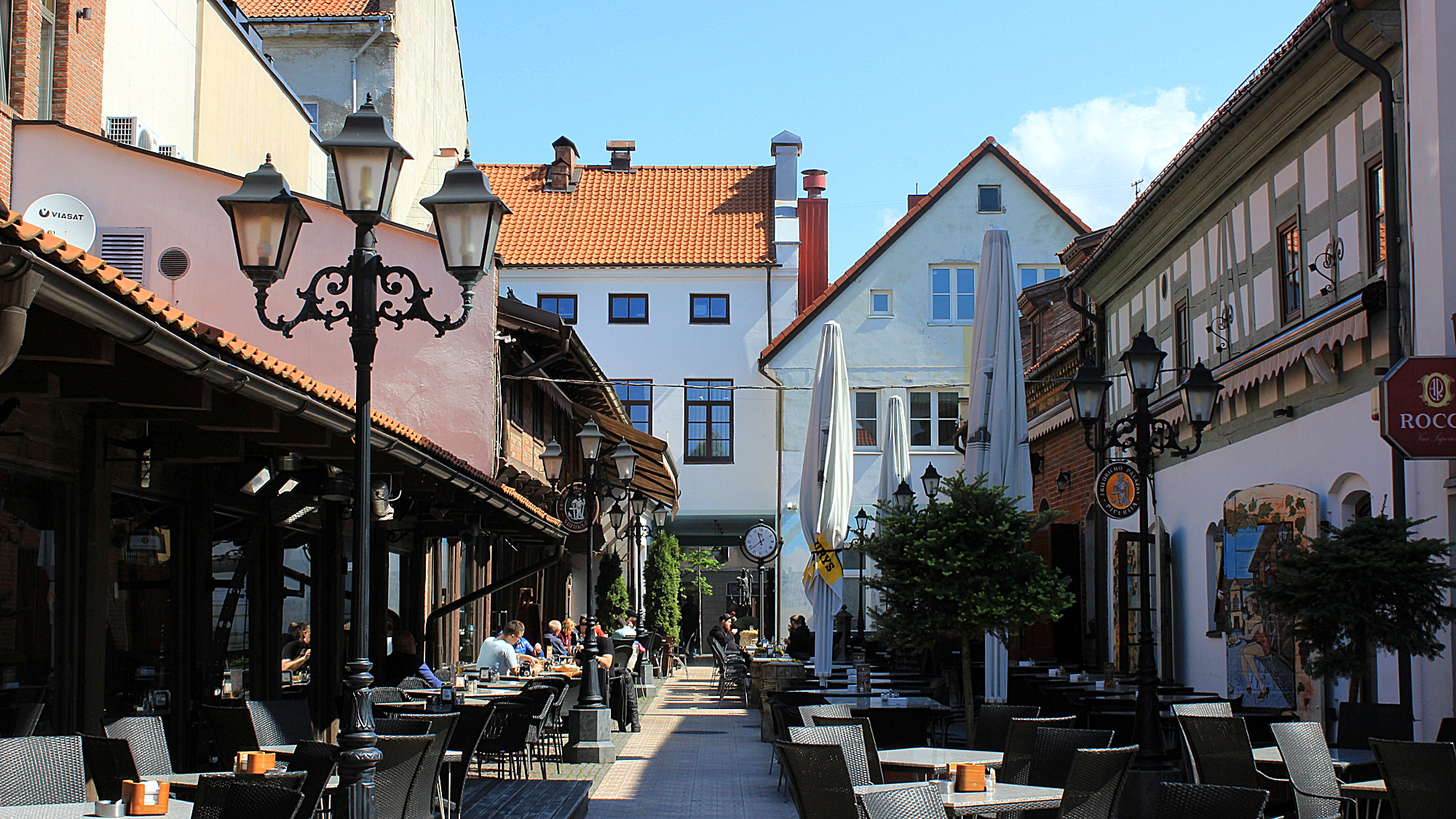 An empty, narrow sidestreet at the Old Town of Klaipeda with beautiful old buildings, an old lamp post and empty cafeteria tables.