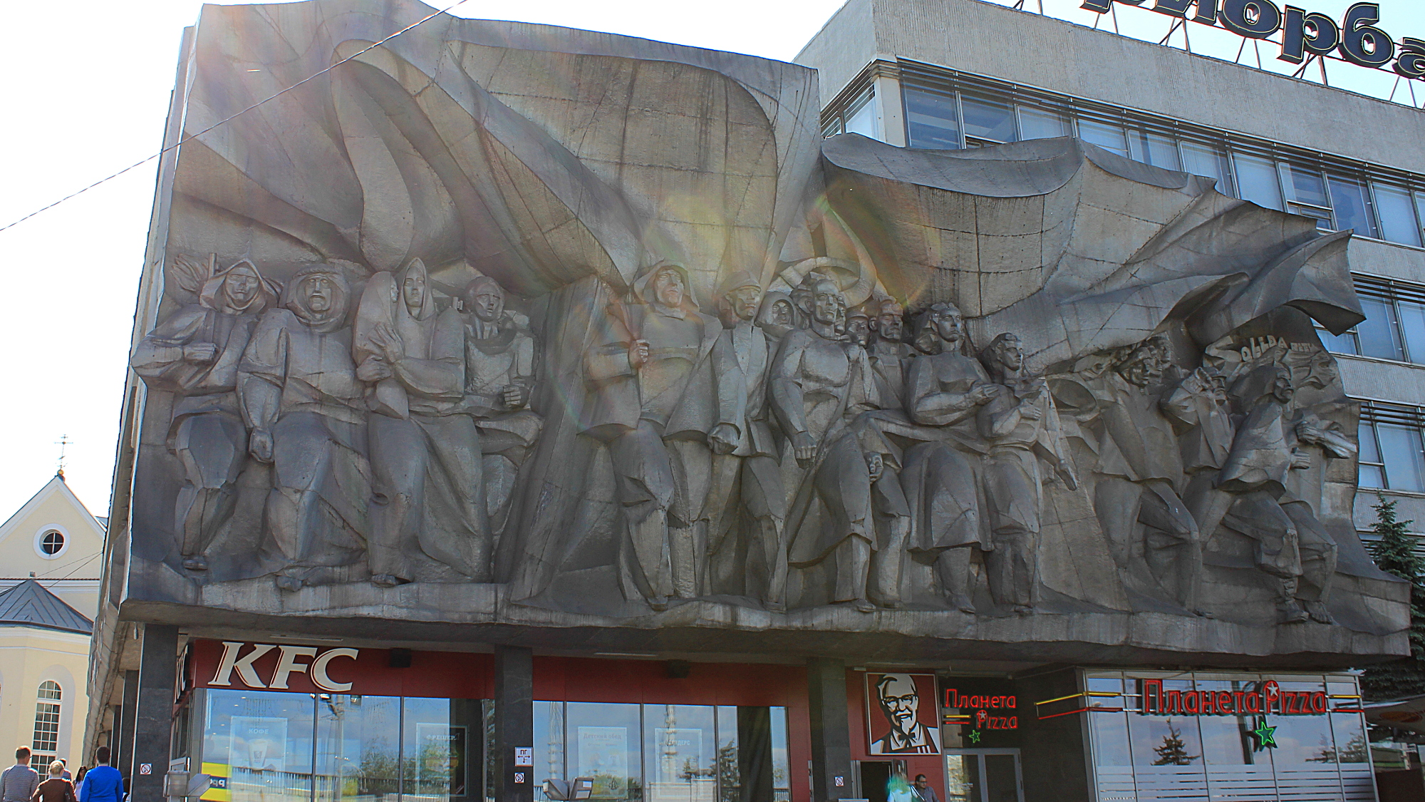 A socialist wall sculpture and a KFC fast food restaurant below it.