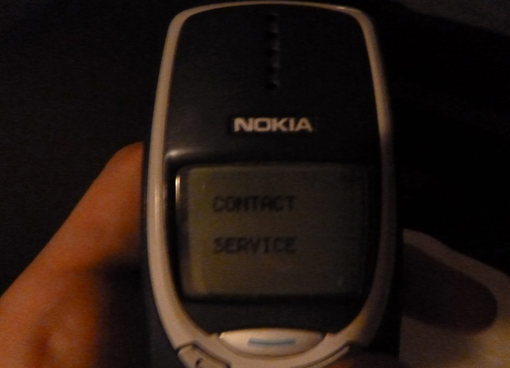 A broken Nokia 3310 with a Contact Service error message.