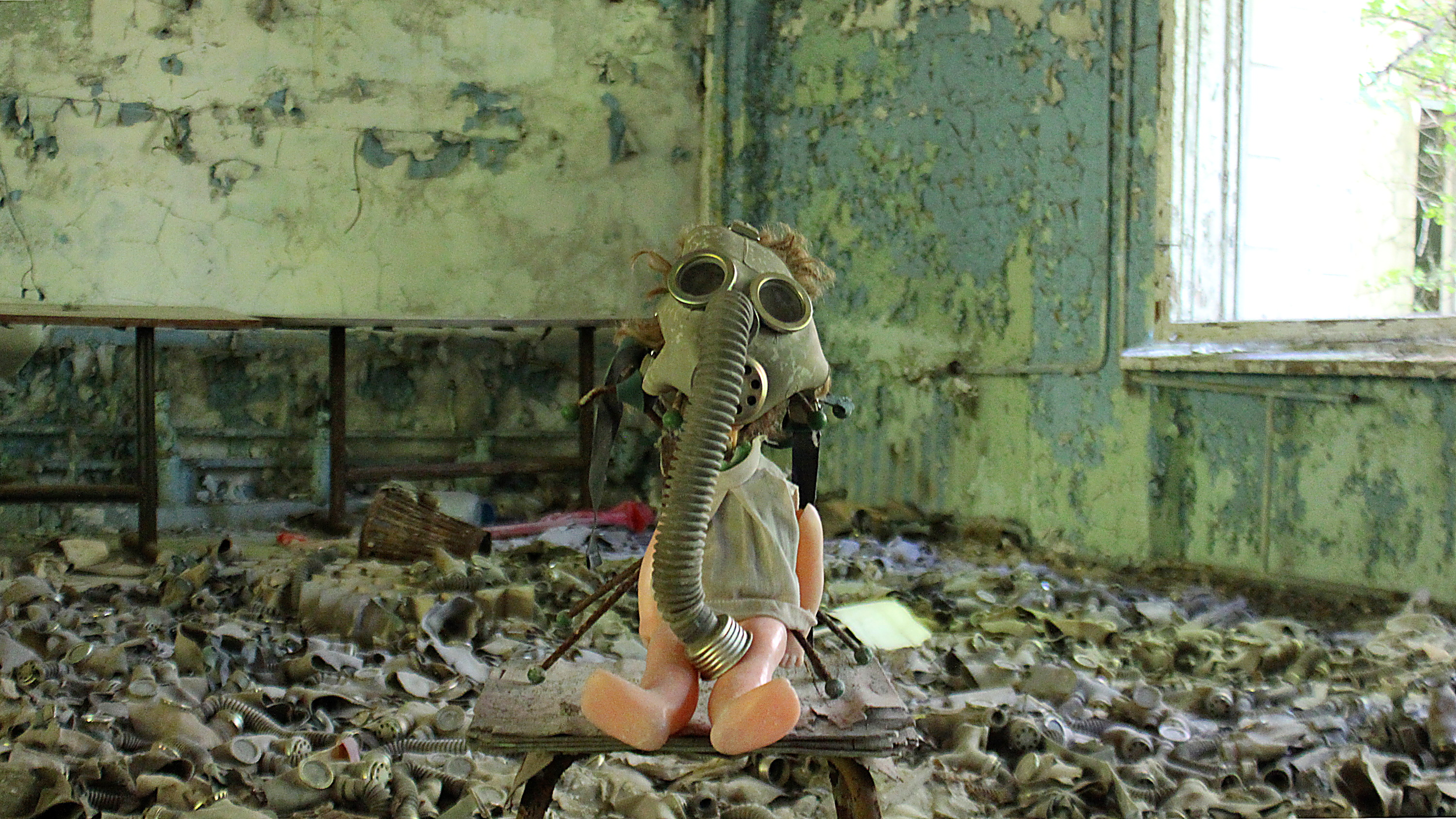 A creepy doll with a gas mask sitting on a chair in a school in Pripyat with more gas masks in the background.