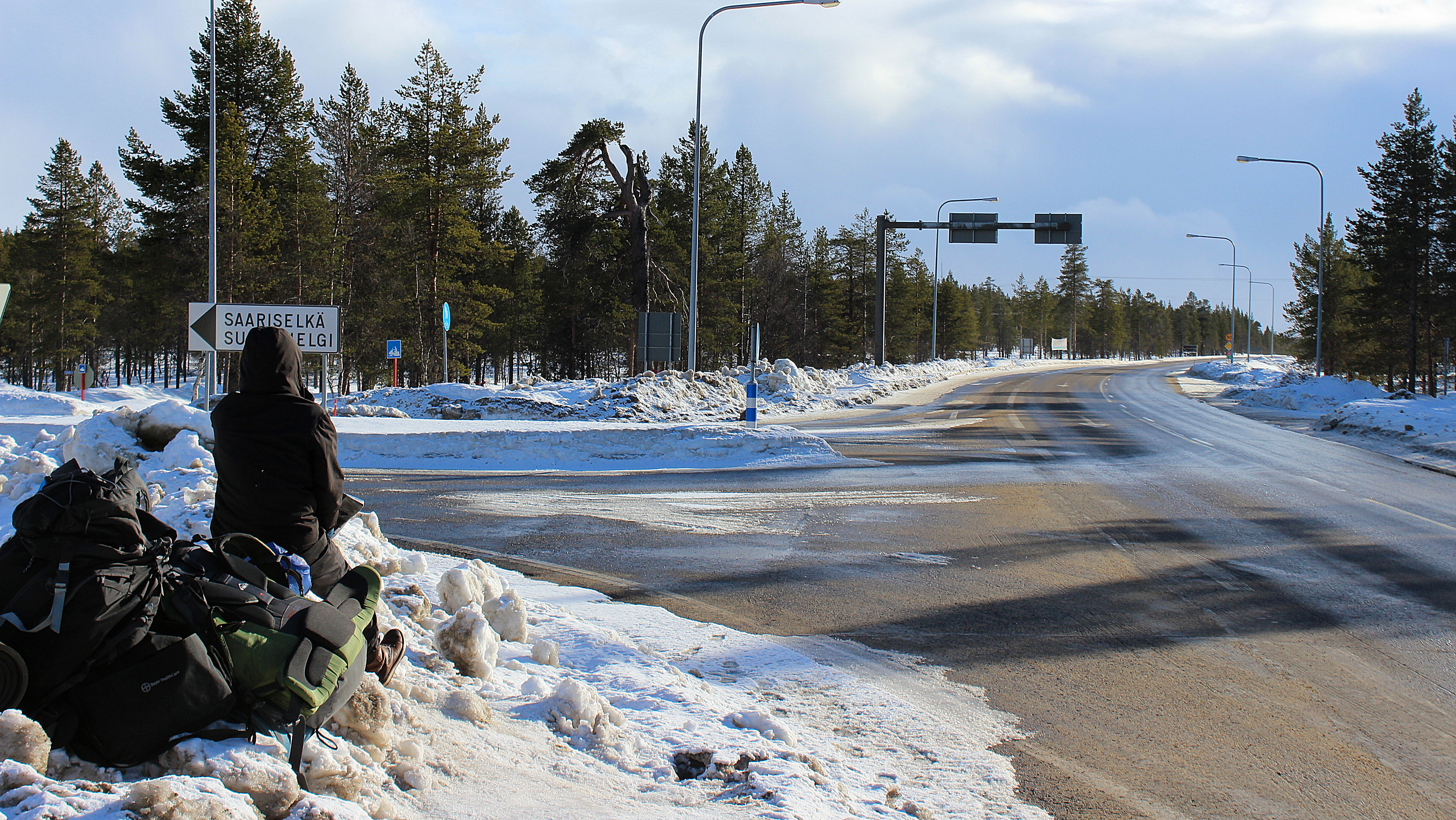 The Saariselkä crossroad in Lapland, Finland with a hitchhiker waiting in the snow for cars to come. / Liftari Lapissa Saariselän risteyksen kohdalla keväthangissa.