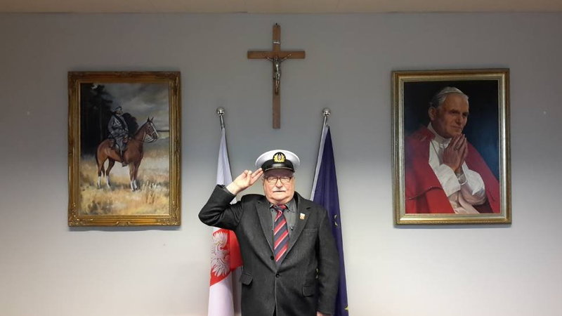 Why Poland is awesome? Lech Wałęsa posing in front of the cross and a painting of Pope John Paul II