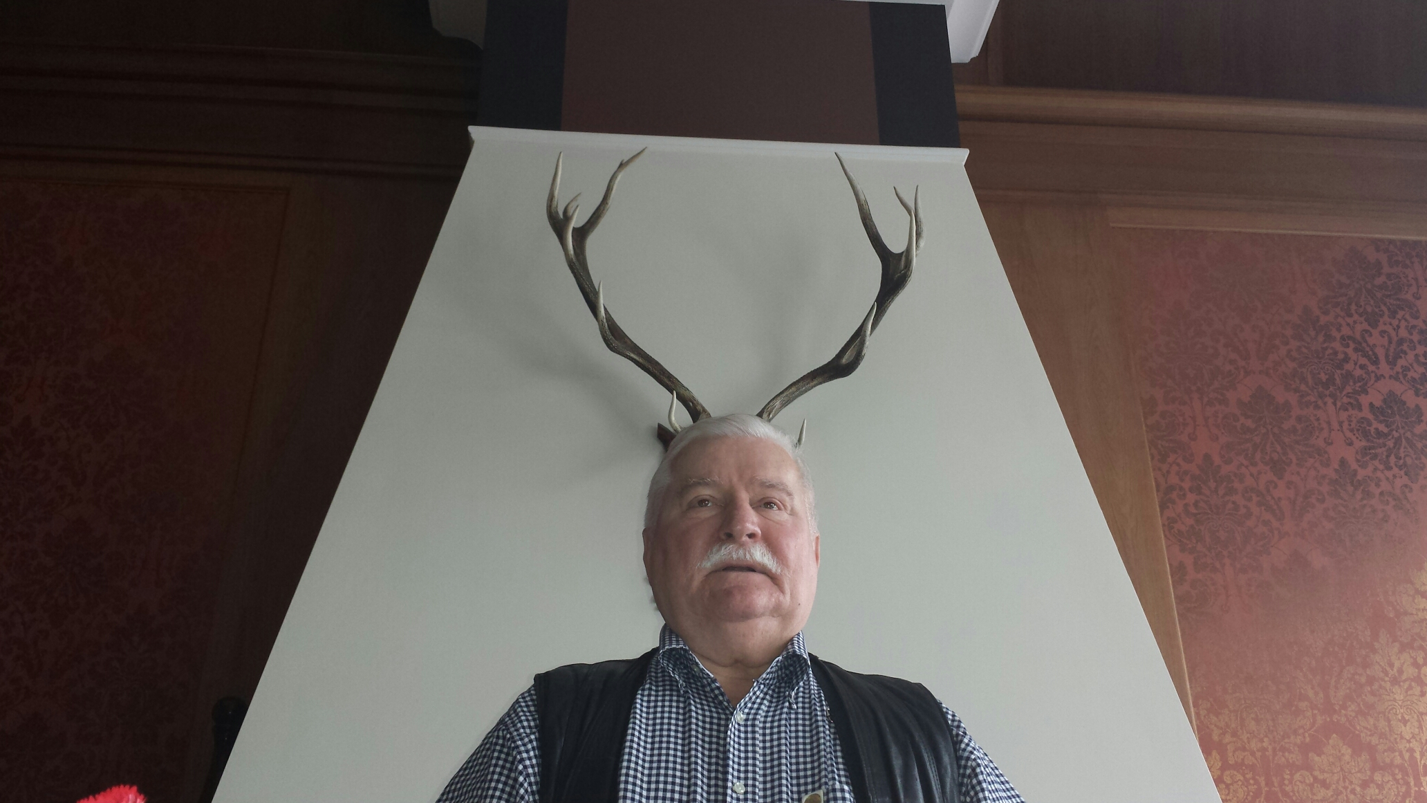 President Lech Wałęsa posing with deer or moose horns behind his head.