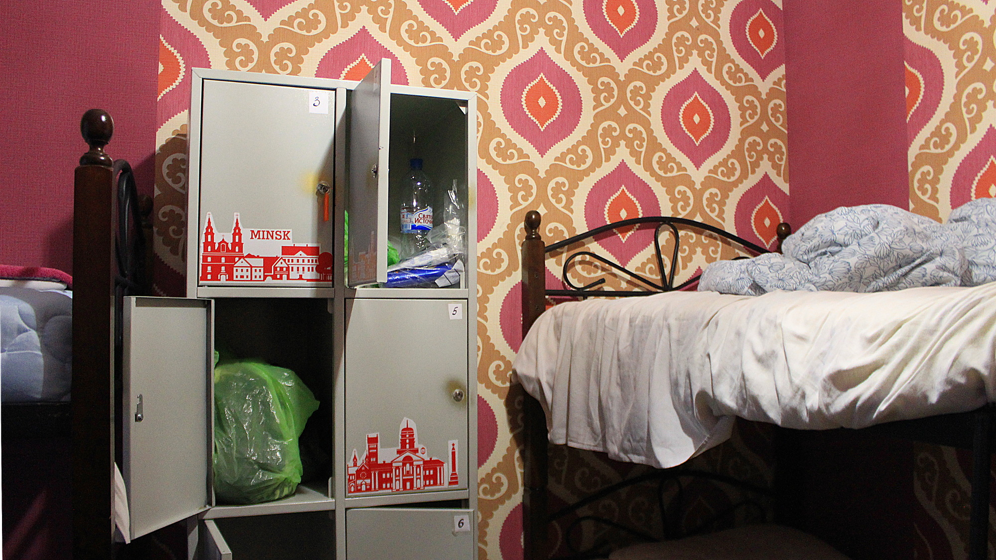 I recommend visiting Eastern Europe. Backpacker hostel lockers in Belarus, Minsk with red and yellow tapestry in the background.