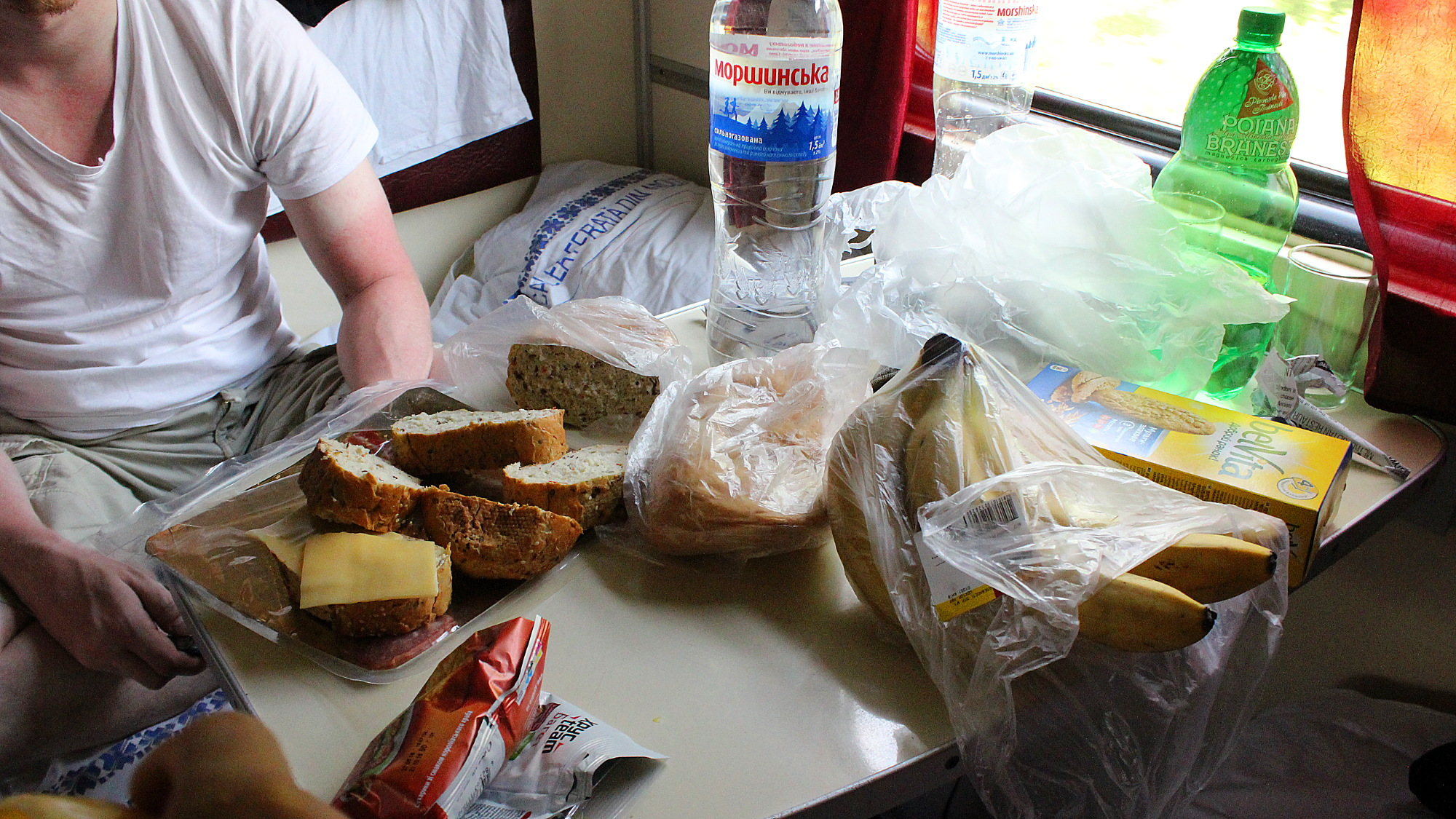 Things to do on long train journeys. Bread, bananas and other snacks spread on a train table in a sleeper car.