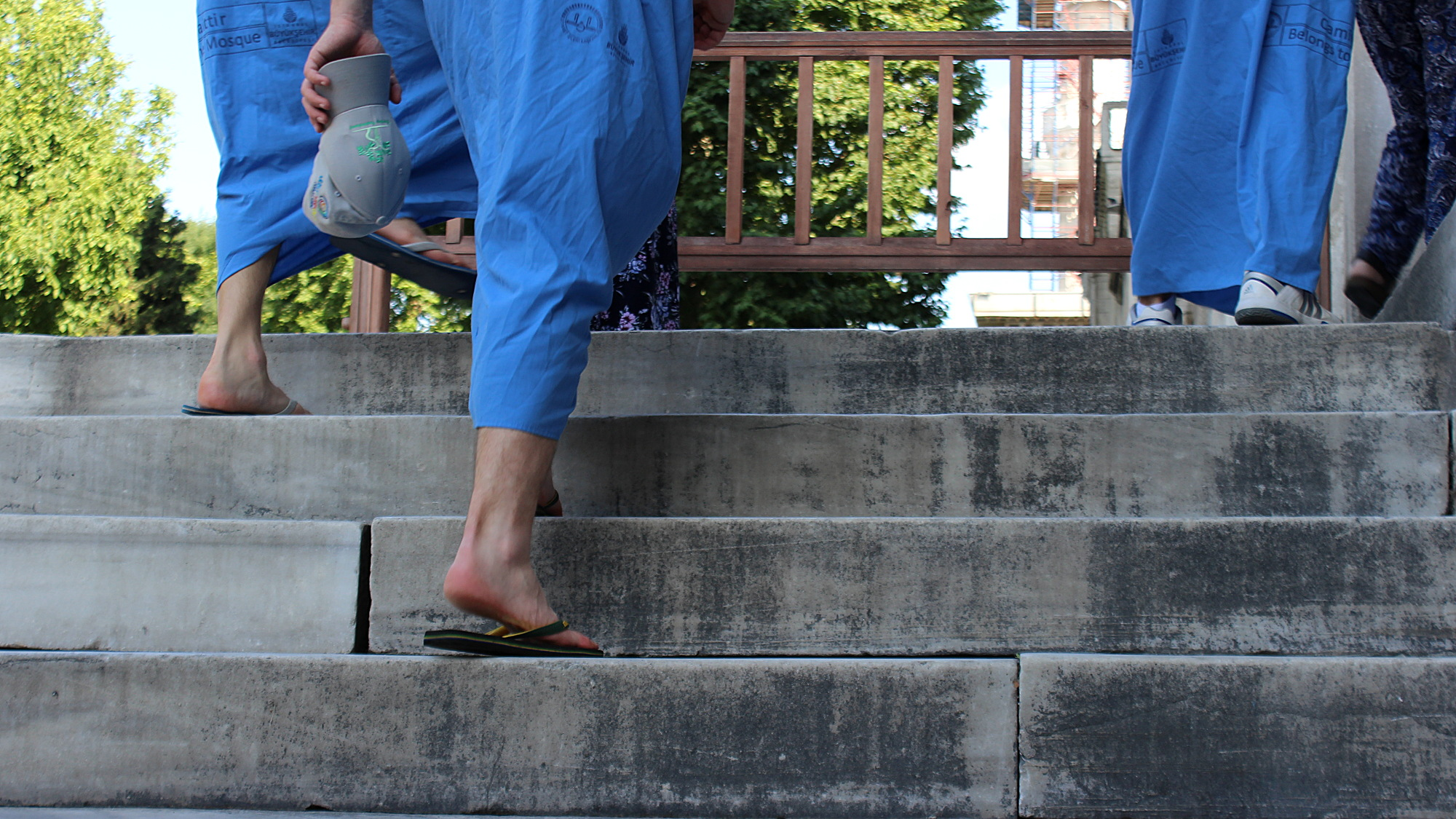 Entering blue mosque without shoes and shorts with blue dresses.
