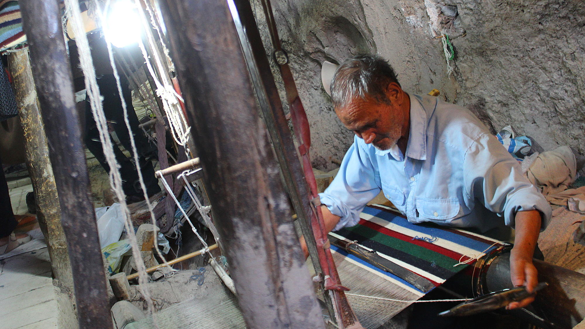 Traditional carpet maker in a cave in Iran.