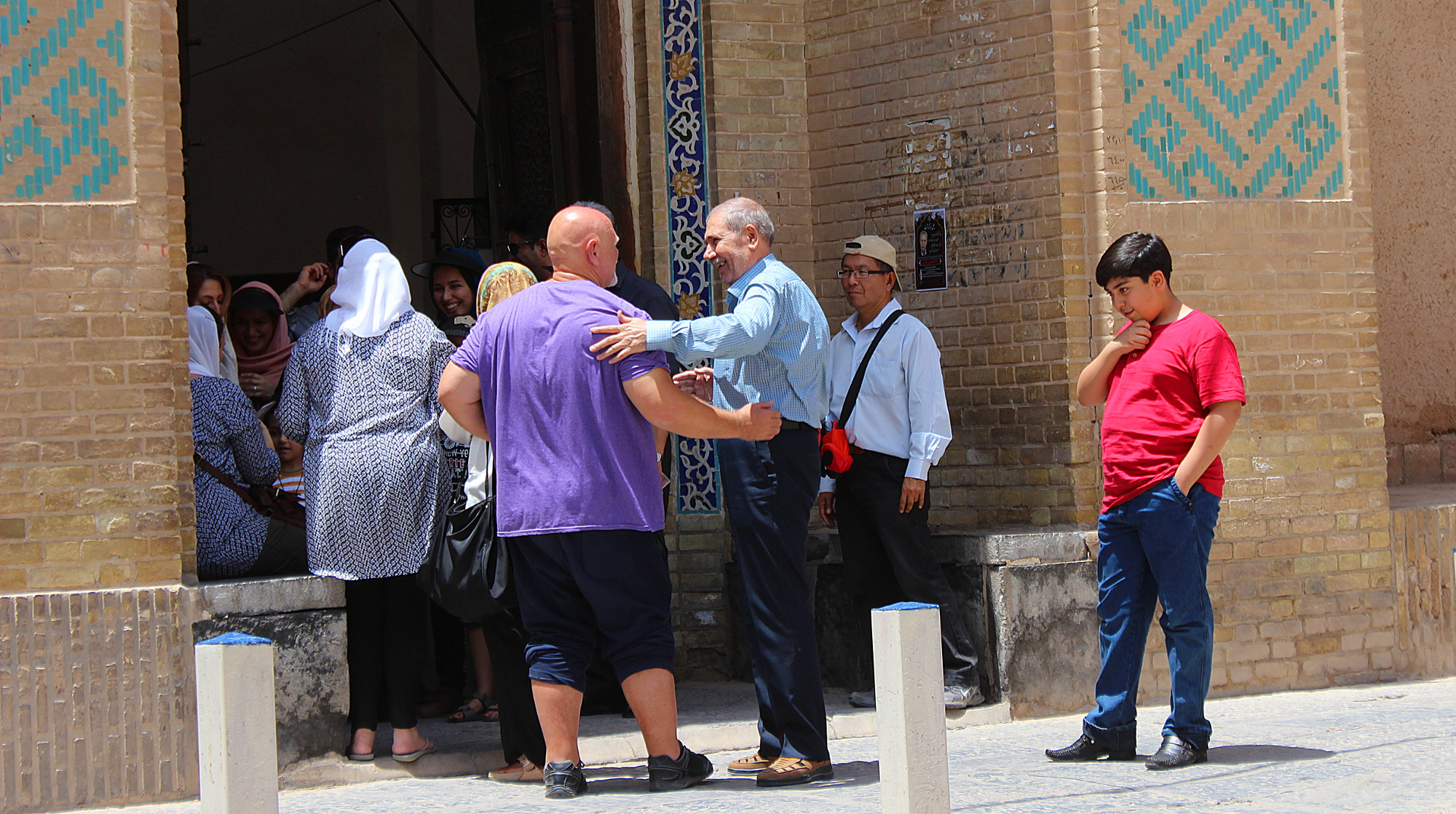 Local Iranian people interacting with tourists who are visiting Iran on a guided tour.