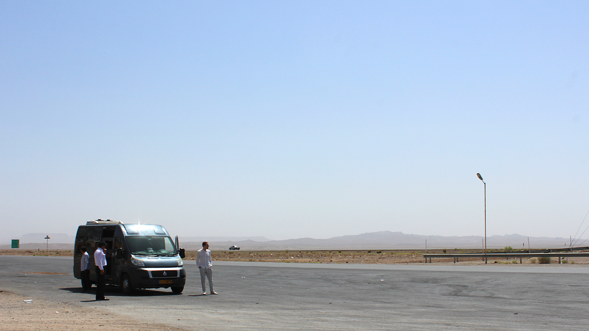 A grey minibus at the side of the road on a desert during a guided tour of Iran.