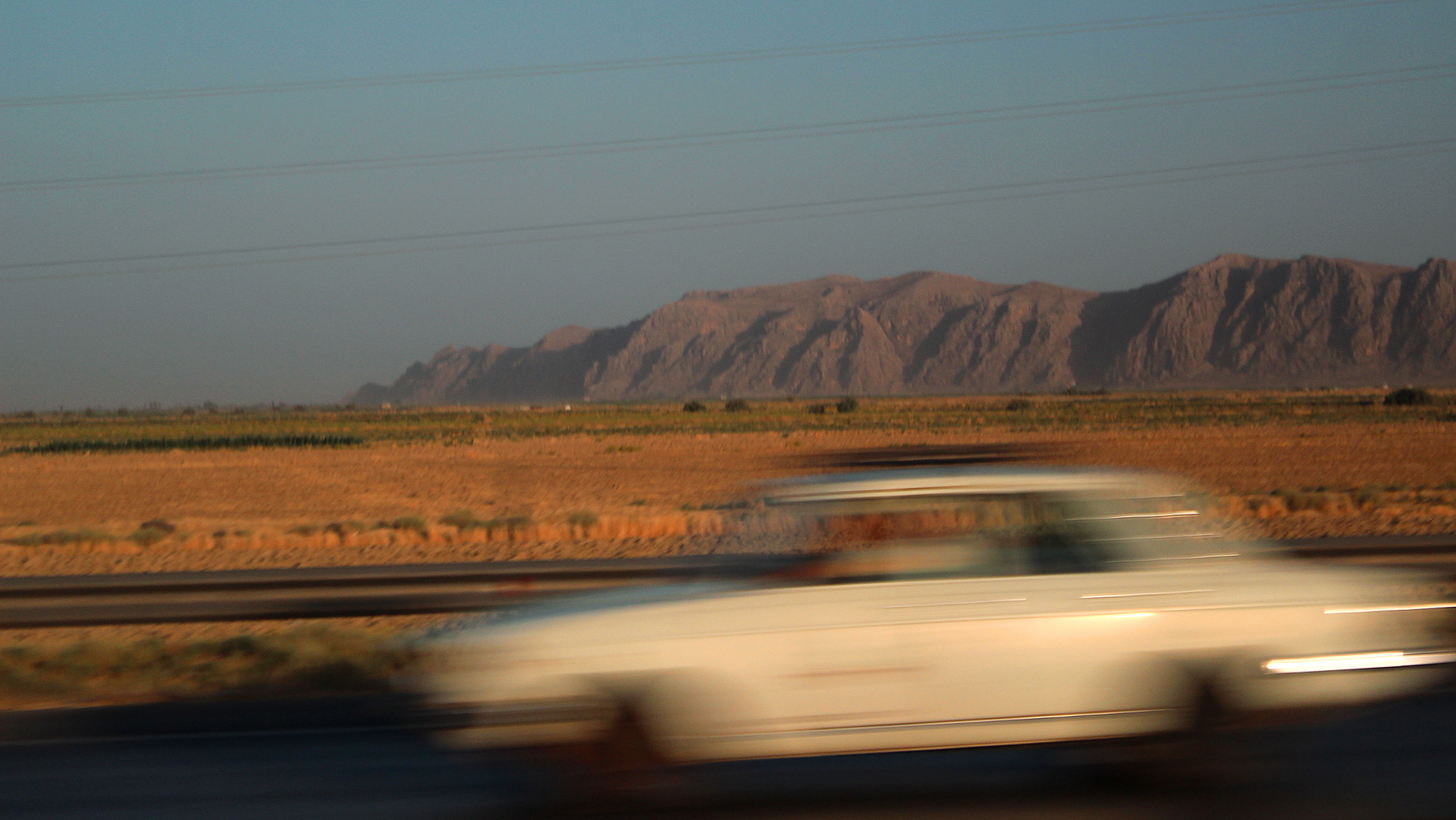 Guided tour of Iran. An atmospheric travel picture of a car driving past with sunset, desert and mountains.