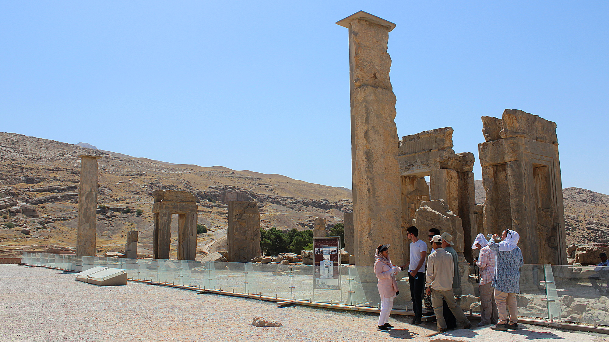 Tourist group taking shade behind a pillar at the ruins of Persepolis.
