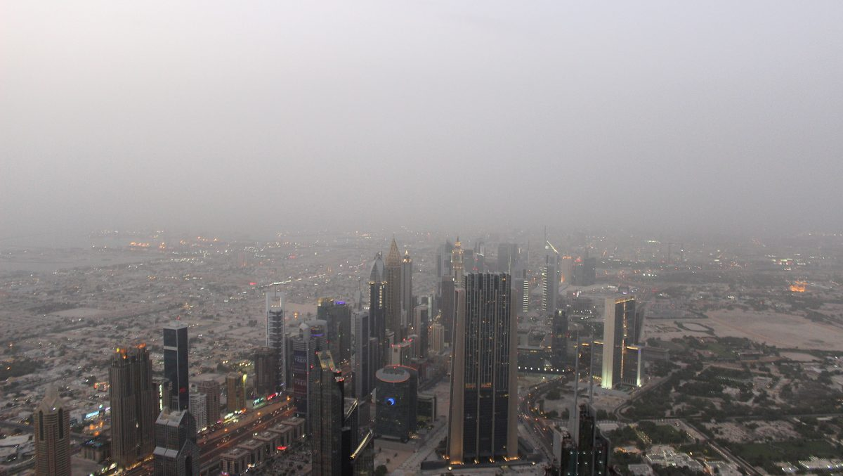 Not the best season to visit United Arab Emirates. View down from Burj Khalifa to other skyscrapers during a misty day.