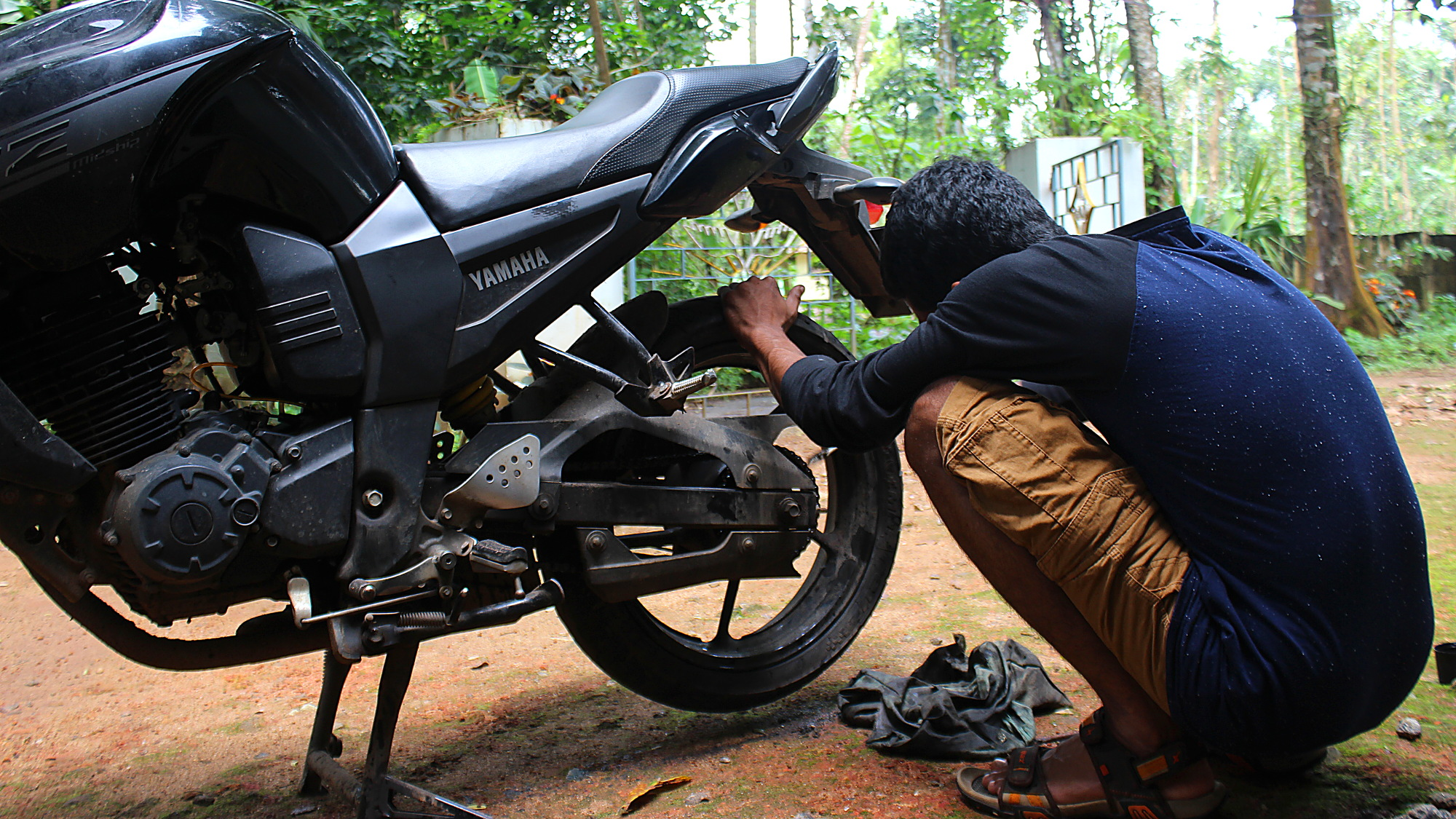 Indian man from Kerala maintaining a Yamaha motorcycle.
