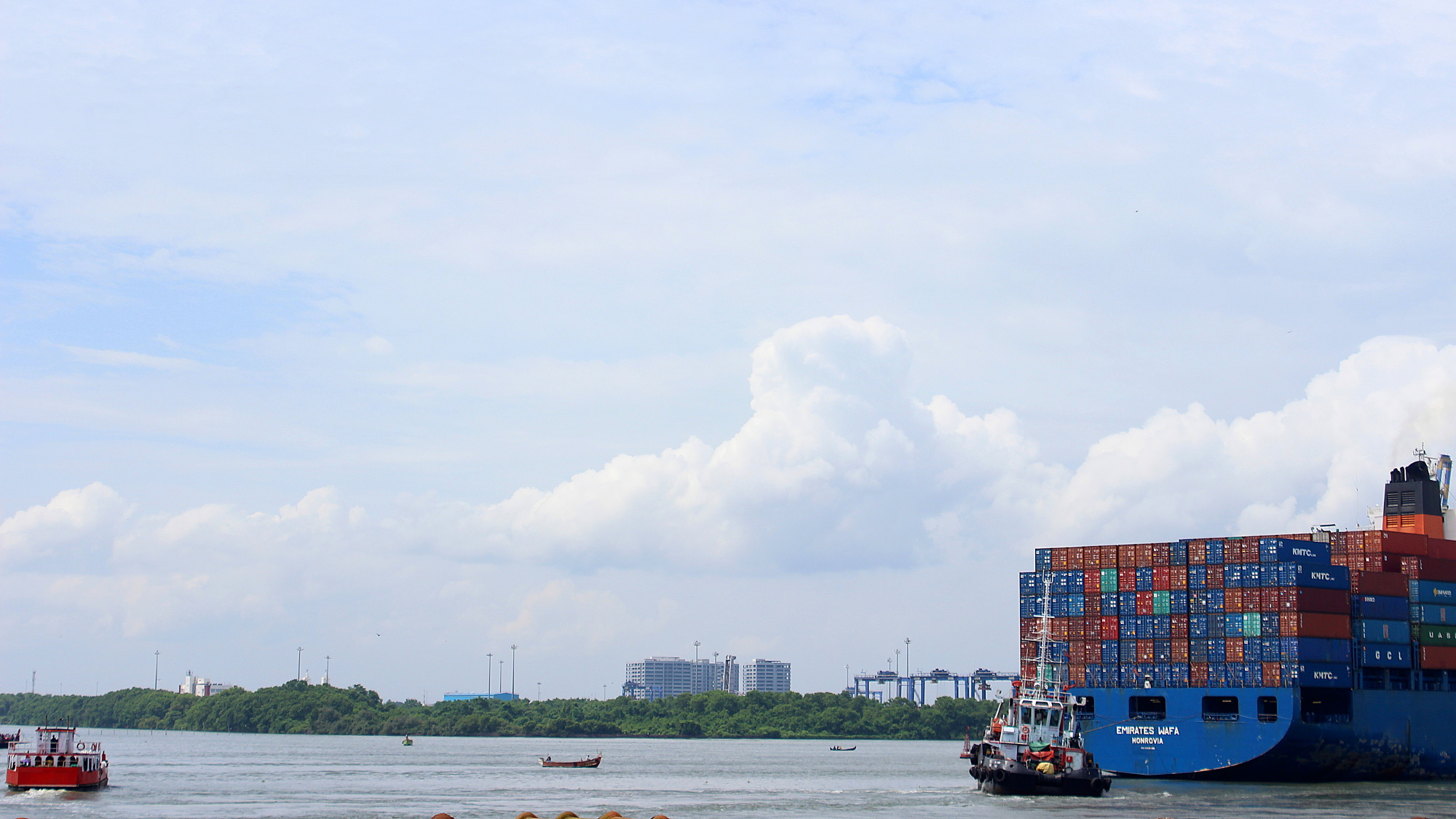 A massive cargo ship disappearing from the frame at the sea in front of Fort Kochi.