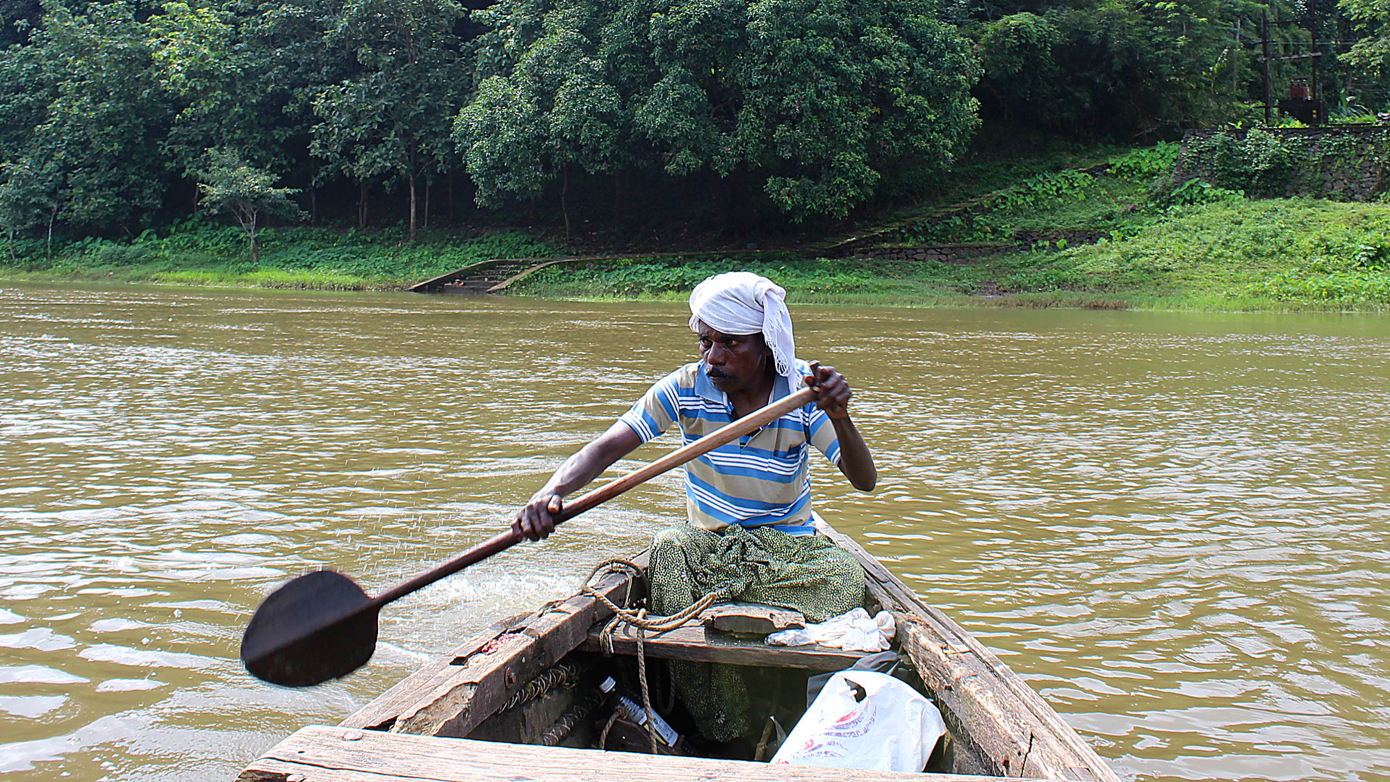 Boatman rowing a canoe boat to the elephant orphanage in Kerala.