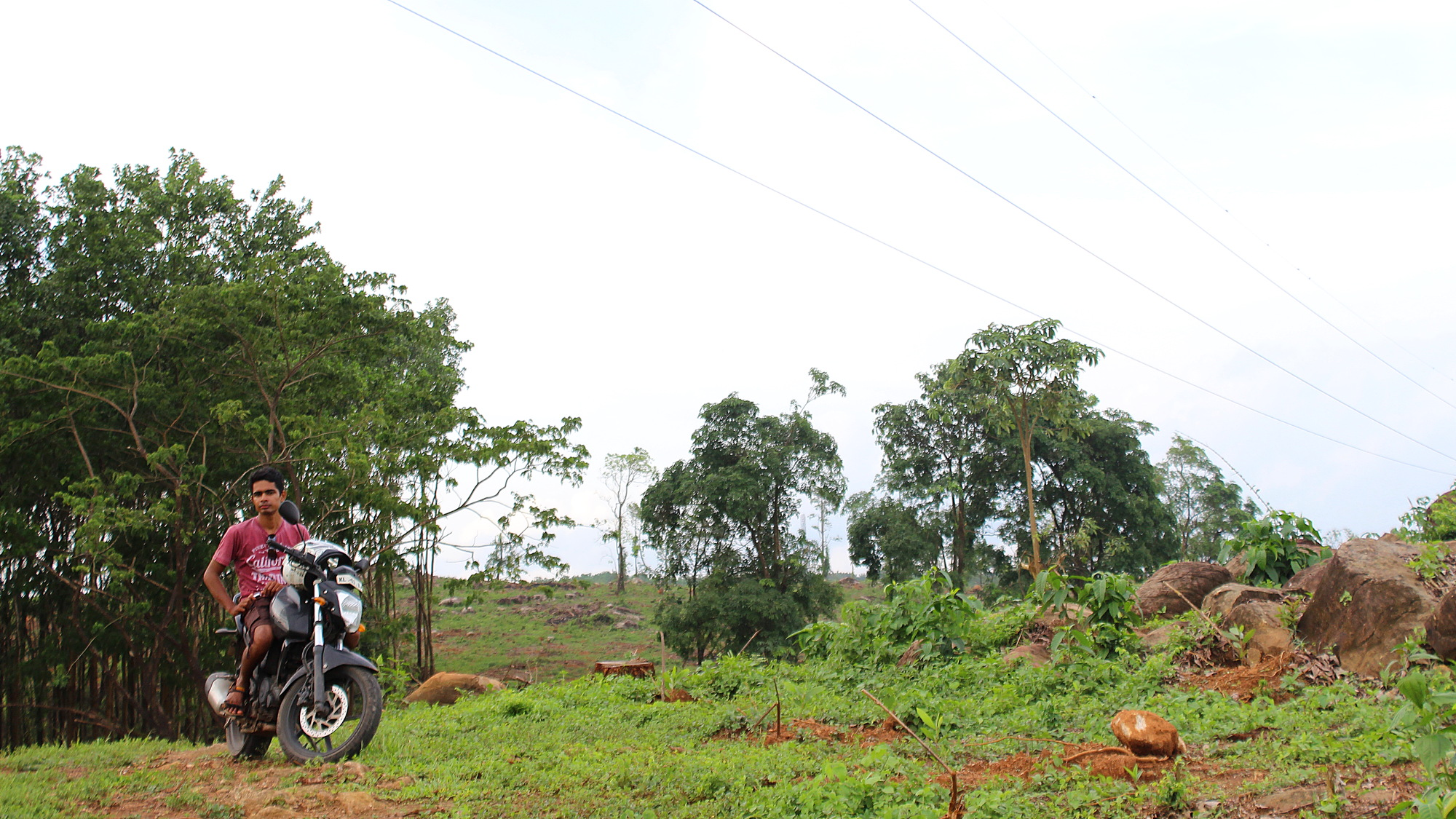 Monsoon travel in Kerala. A young man from Kerala posing in a green hill with a motorcycle.