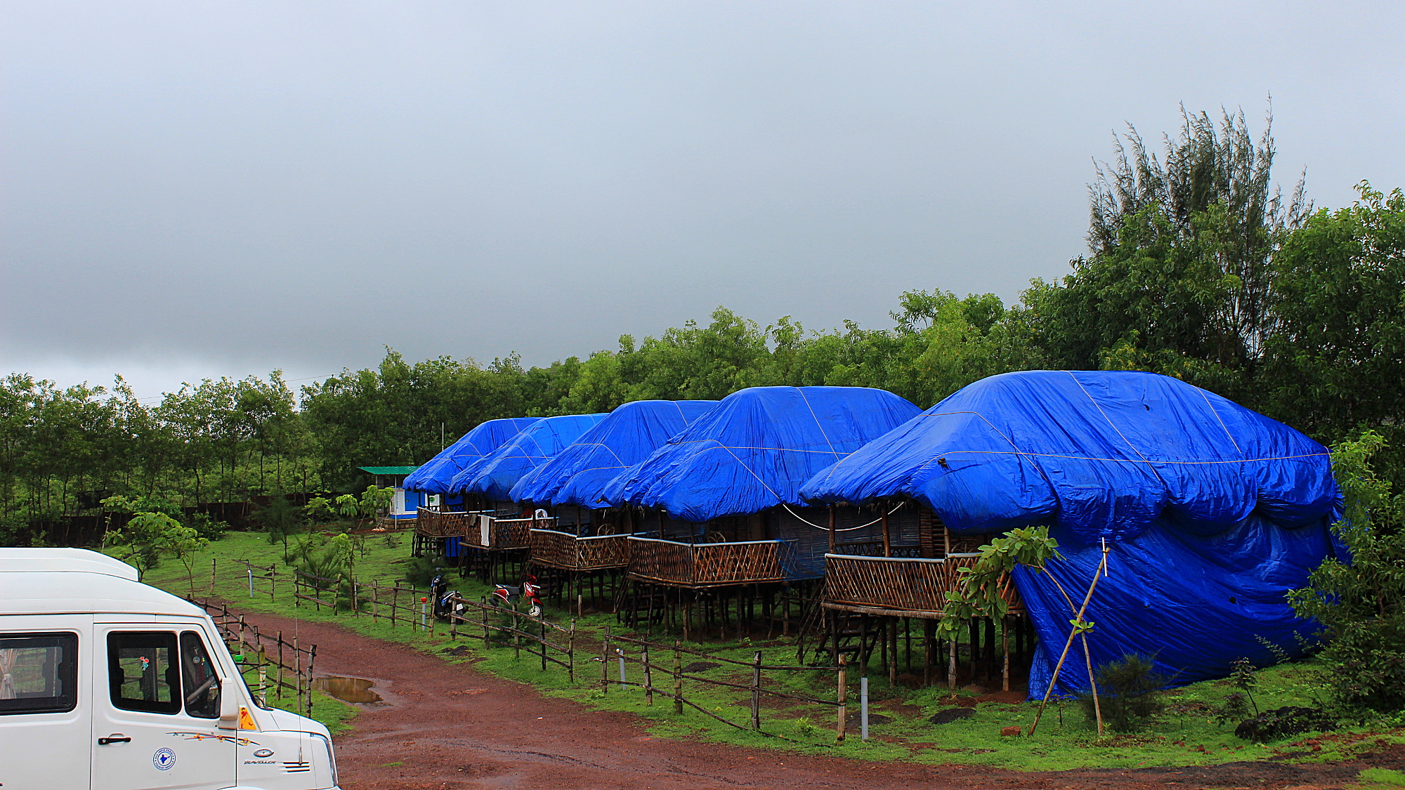 The bungalows of Zostel Gokarna covered with blue tarps for the rain during the Monsoon season.