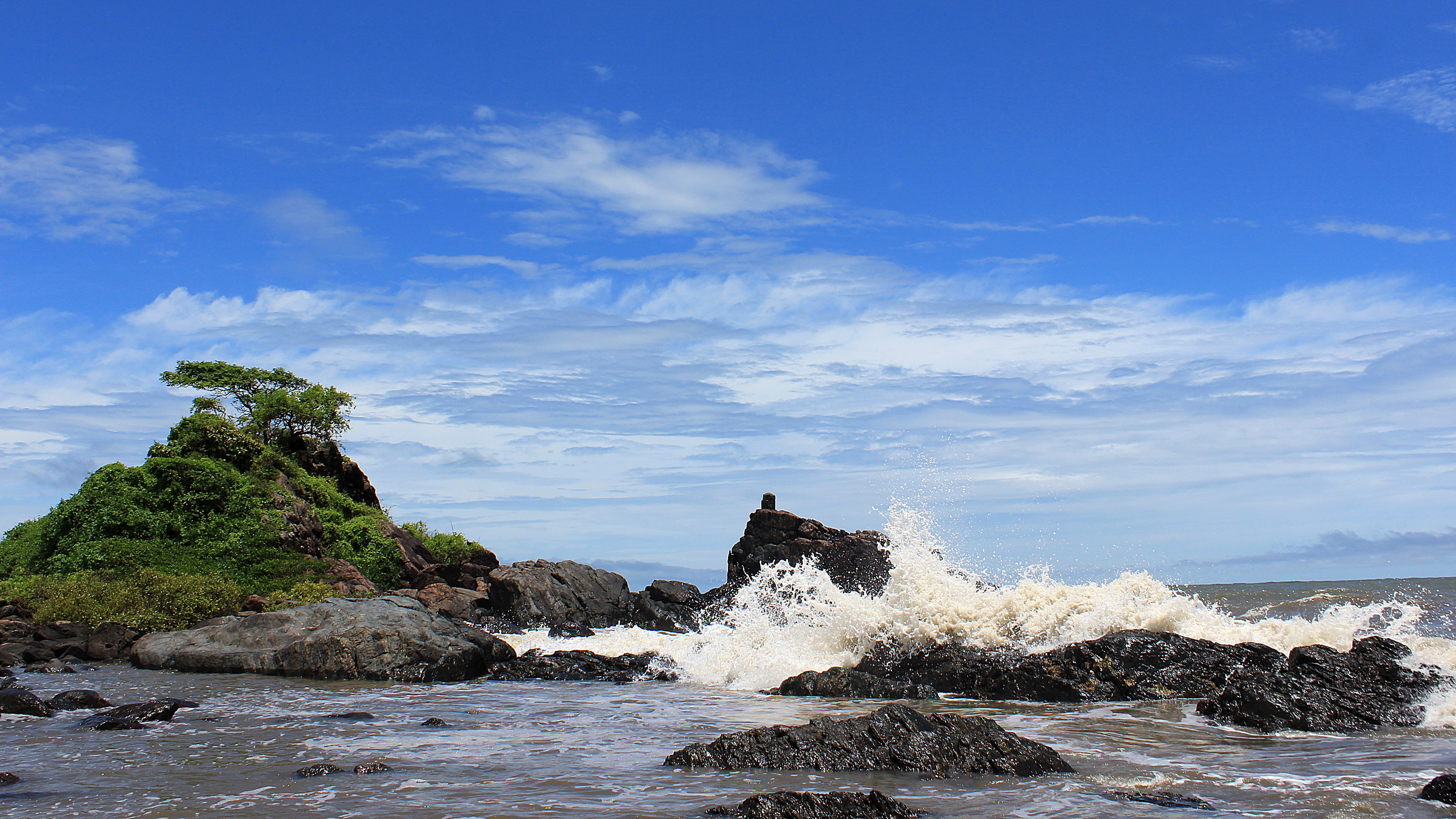 A wave hitting the rocks at Om Beach with a small green hill by the coast.