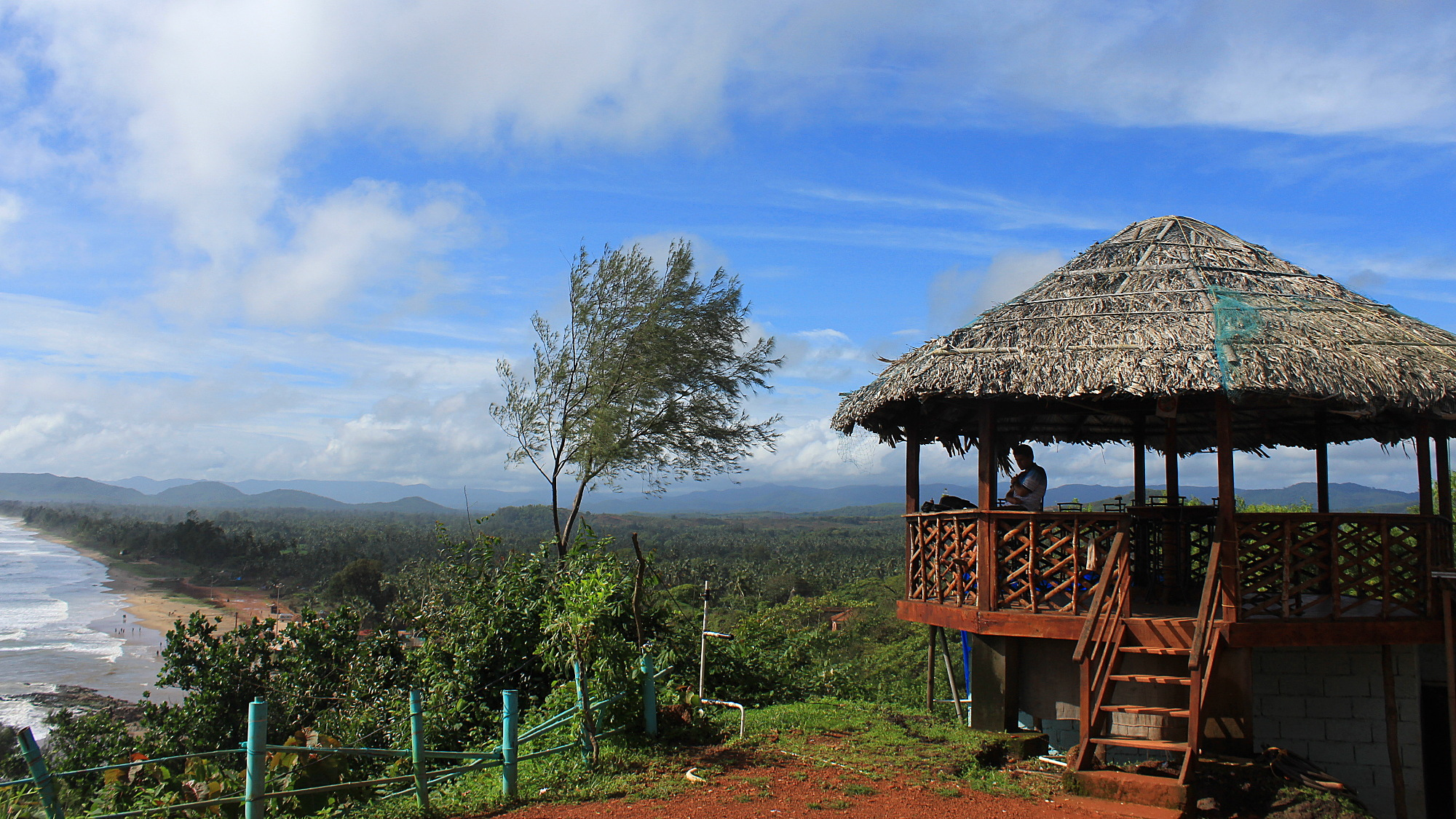 The yard of Zostel Gokarna with blue sky and a viewpoint restaurant hut on the hill.