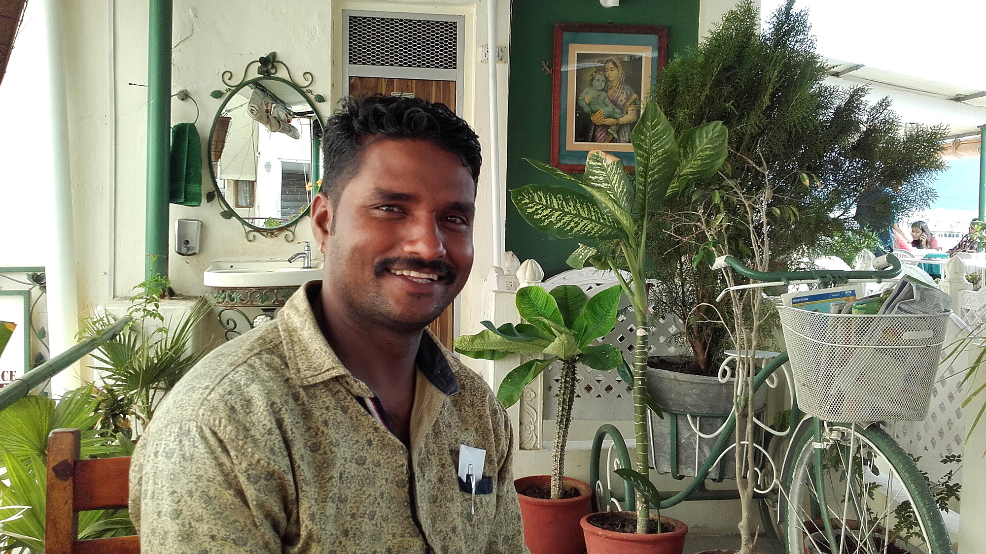A smiling Indian man with a mustache in a restaurant.