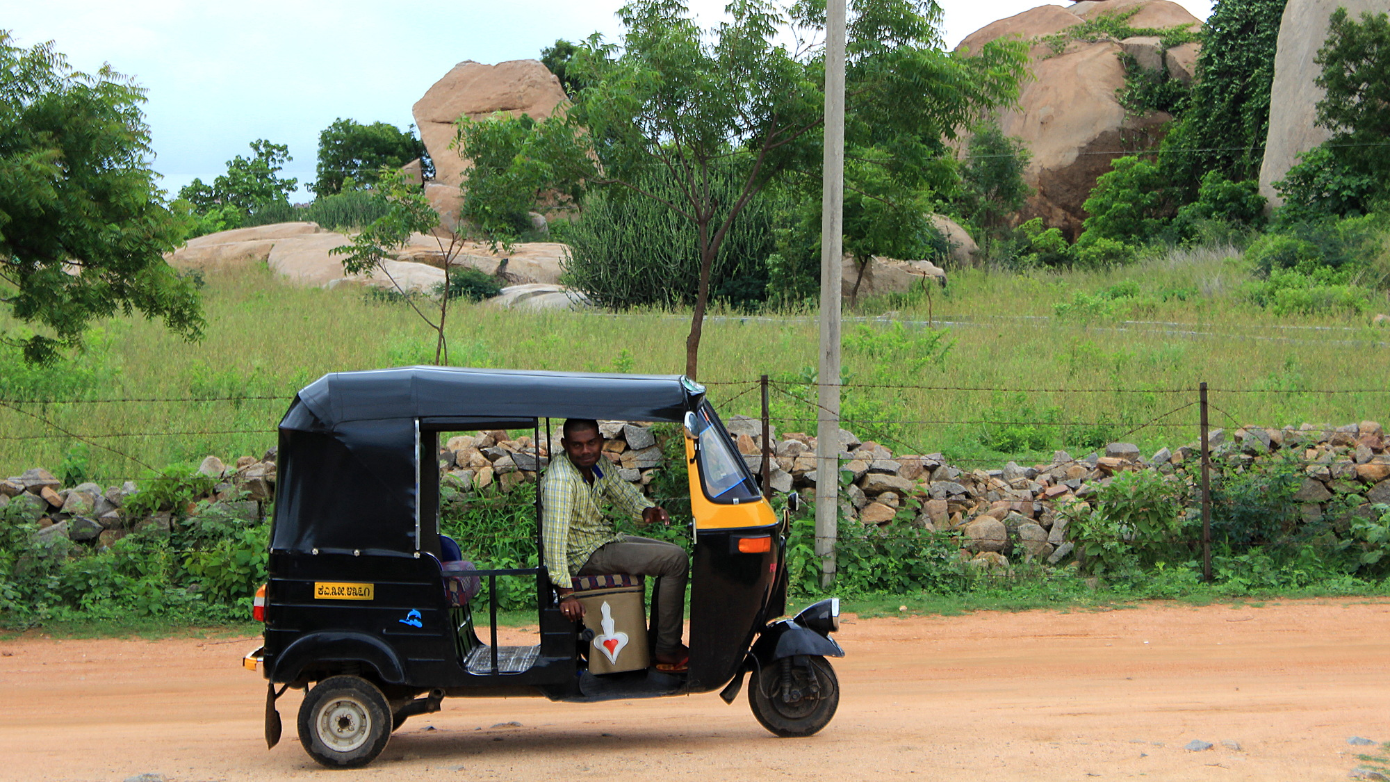 A black and yellow rickshaw parked on a hill with the driver looking at the camera. Photographed from the side.