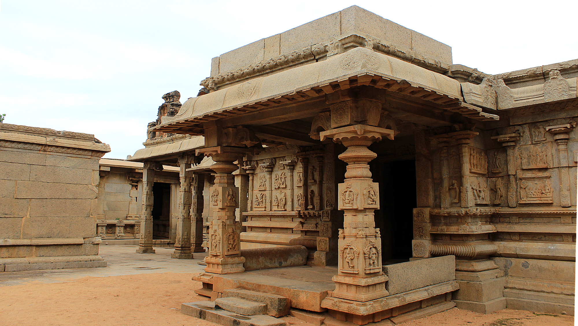 The ruins of Hampi. Light brown exterior of the Hazarama Temple with carved pillars.