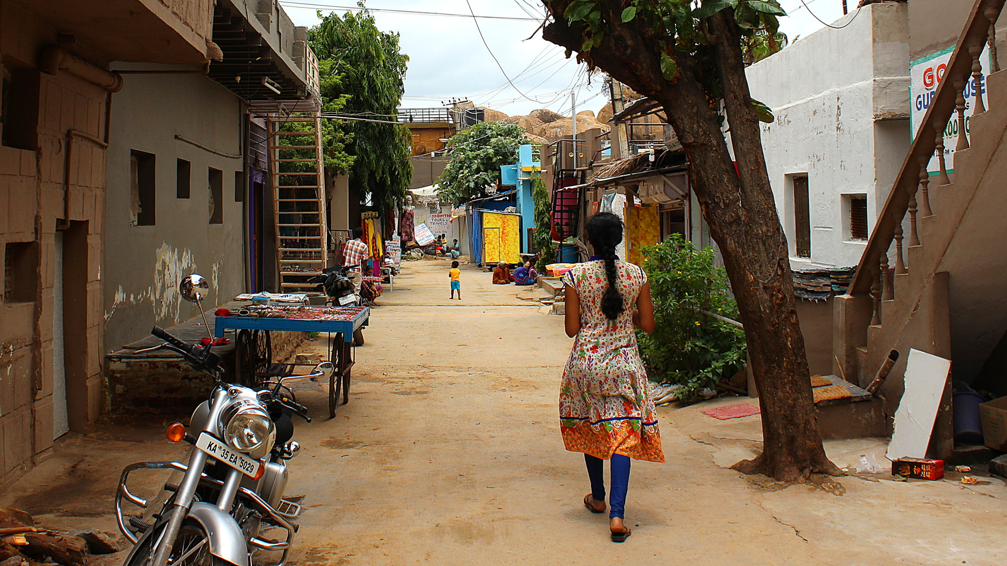 A quet street in Hampi Bazaar with a local woman walking away from the camera.