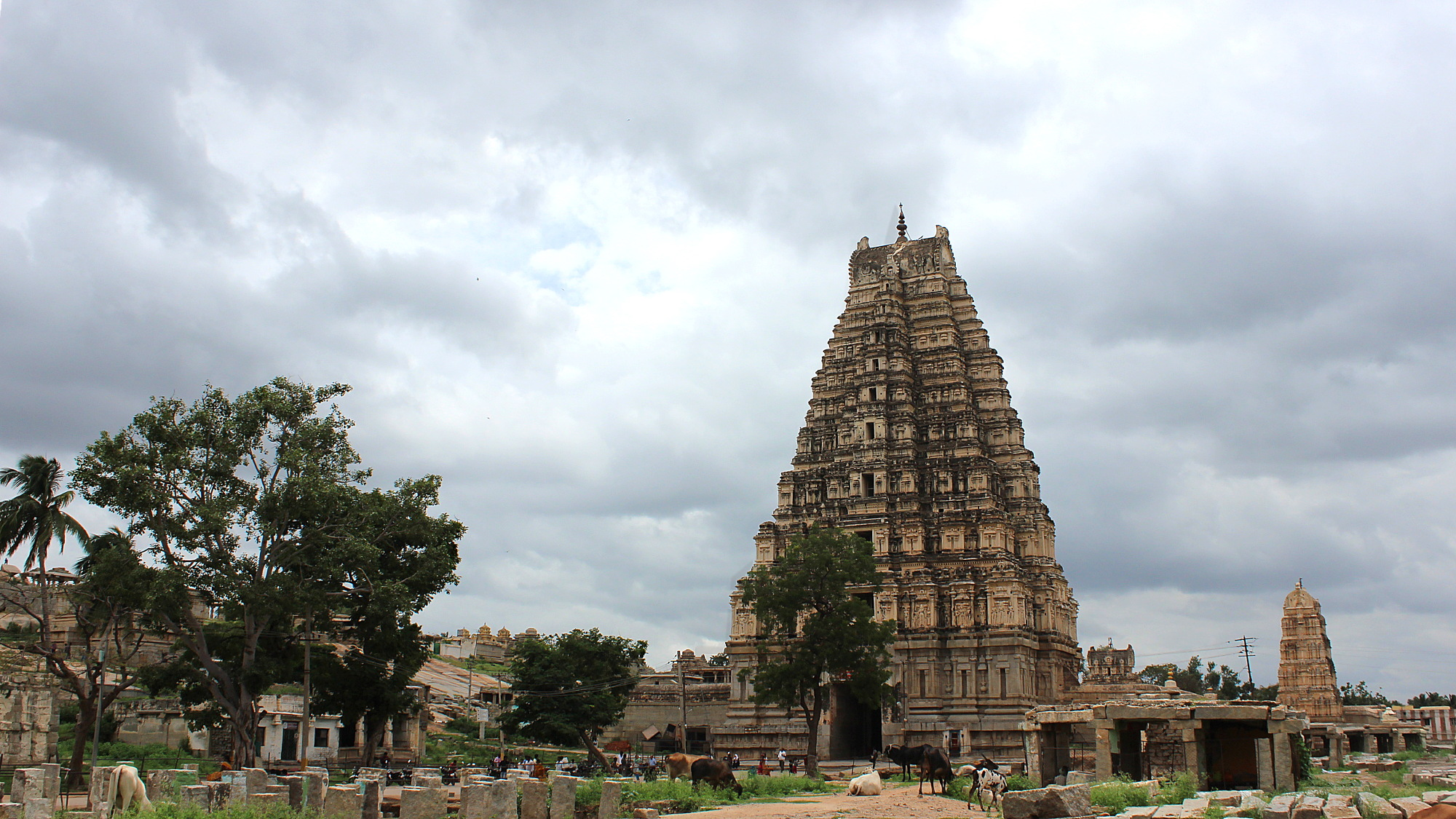 The Virupaksha Temple tower in Hampi with grey clouds in the background. The temple was built when Hampi was the capital of Vijayanagar empire.