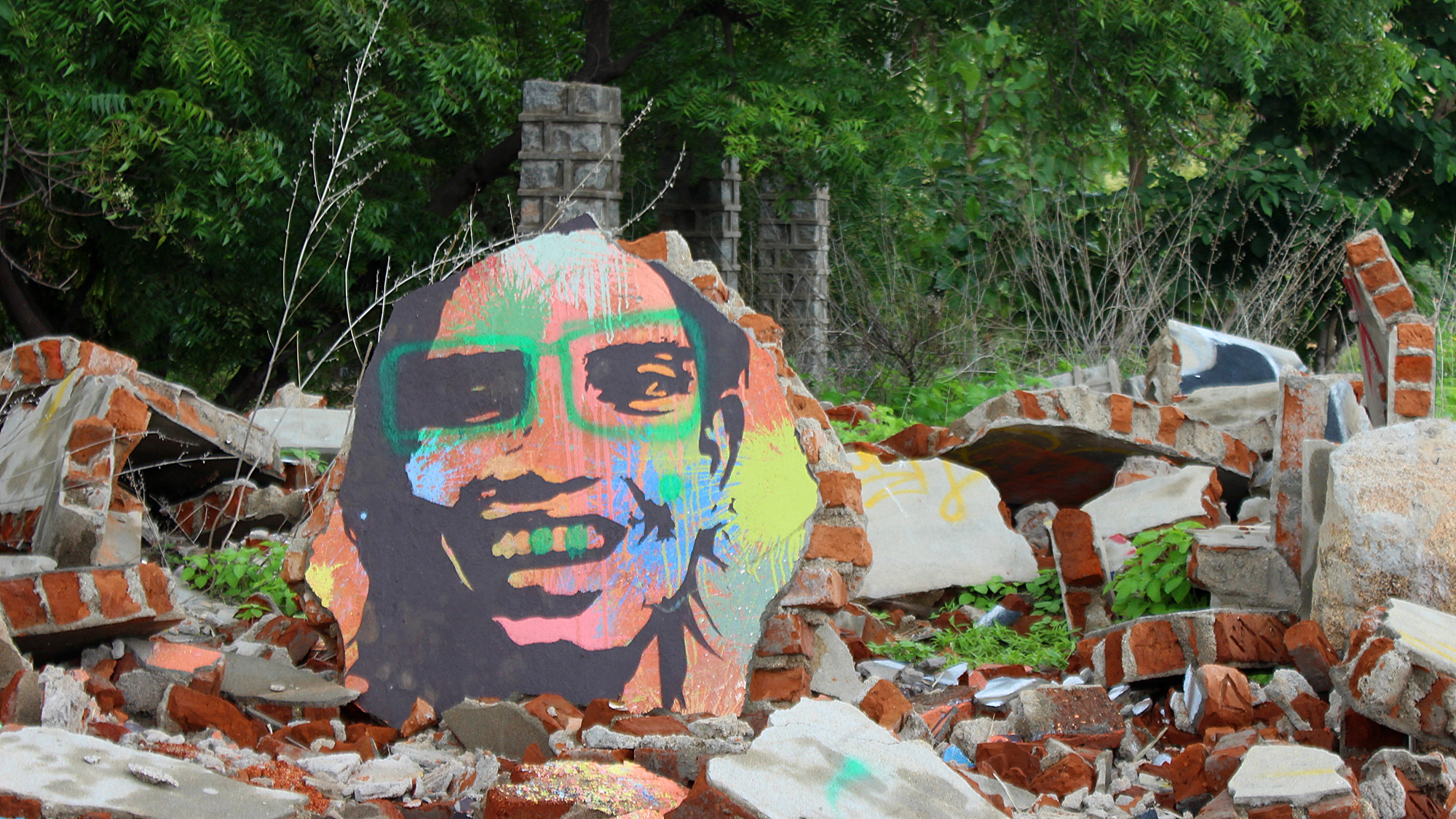 A colorful graffiti of a smiling man on a piece of concrete in Virupapur Gaddi.