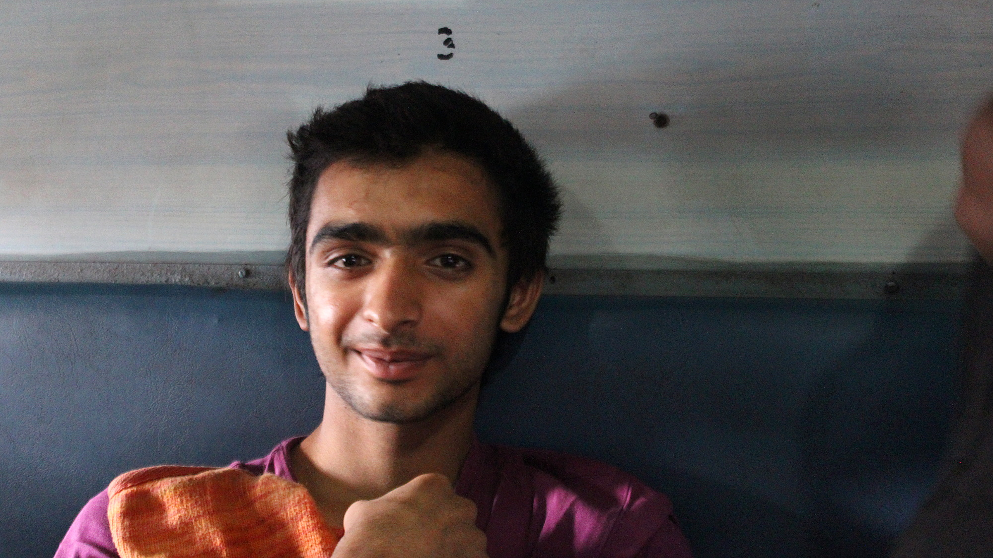 A young Indian man sitting on a second class train carriage.