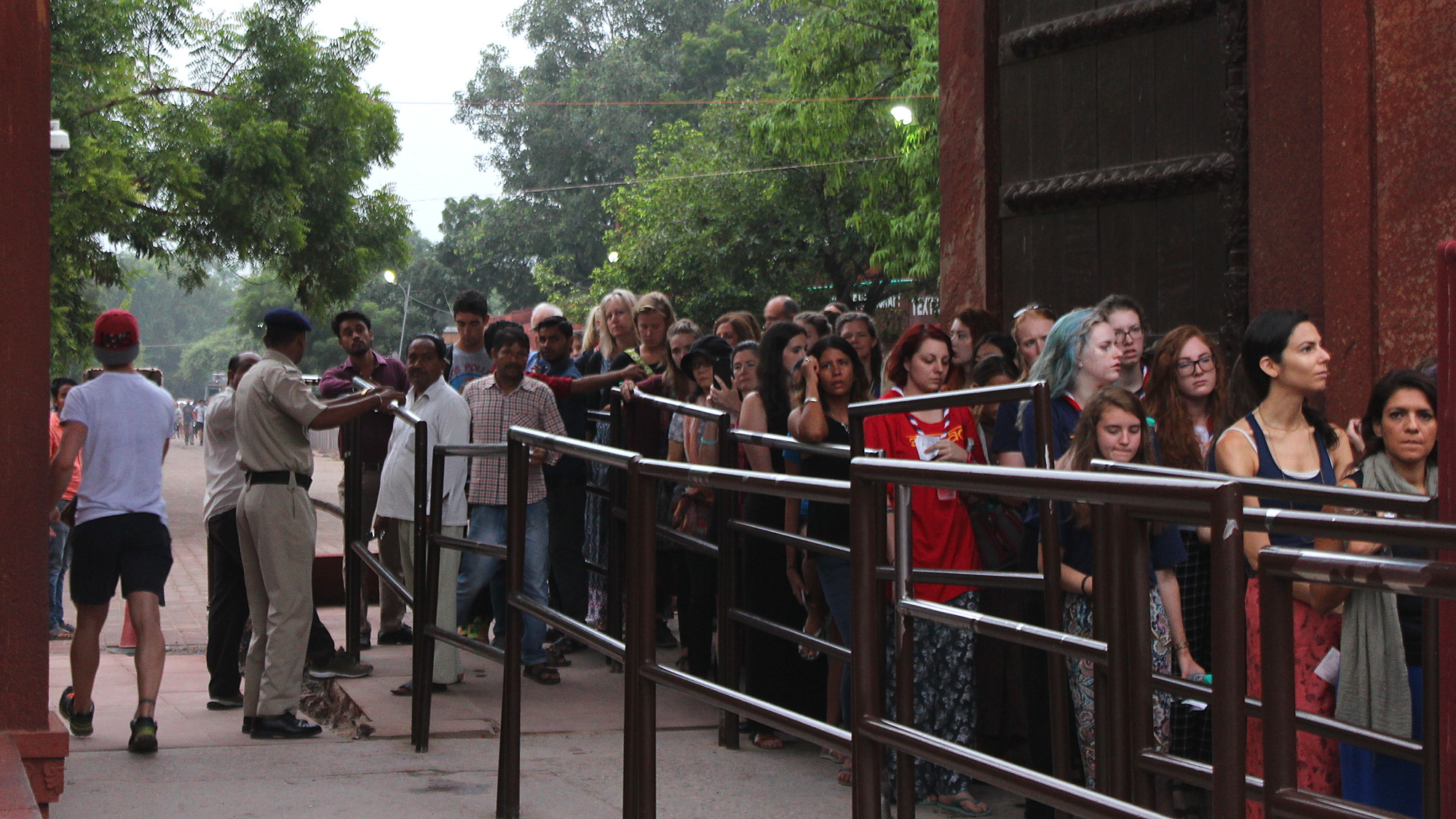Men and women have separate lines at the entrance to Taj Mahal. The line for men is empty at sunrise, while the line for women continues behind the corner.