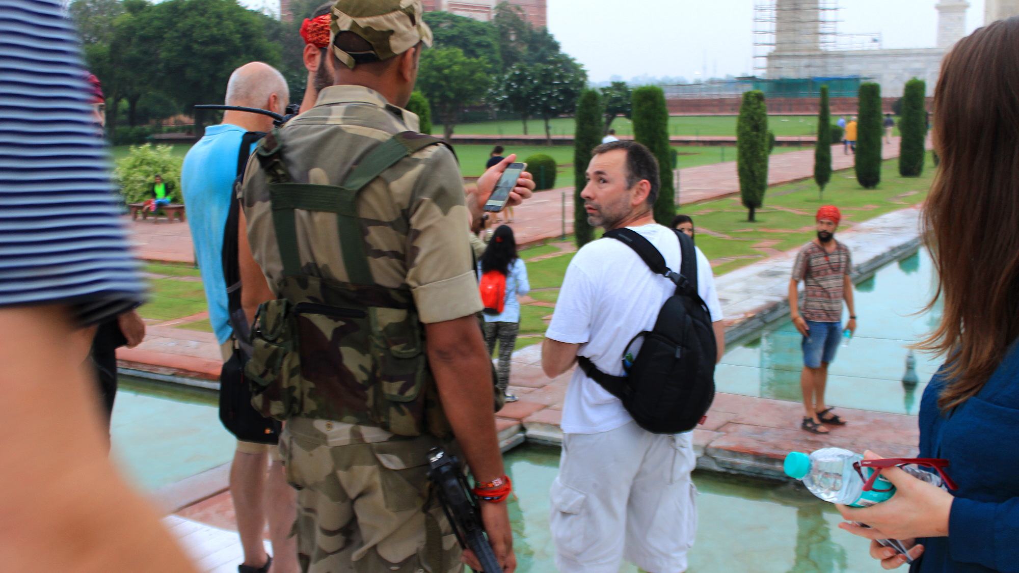An armed soldier asks a group of tourists to delete their photos where they've posed in the lotus position for the camera.
