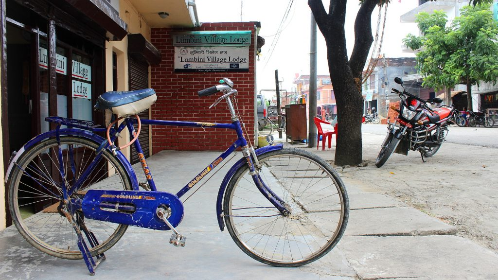 A rented blue bicycle in Lumbini Bazaar in front of Lumbini Village Lodge.