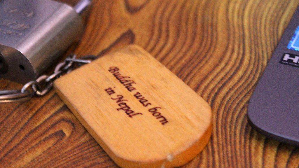 "A wooden keychain for a guestroom key saying ""Buddha was born in Nepal""."