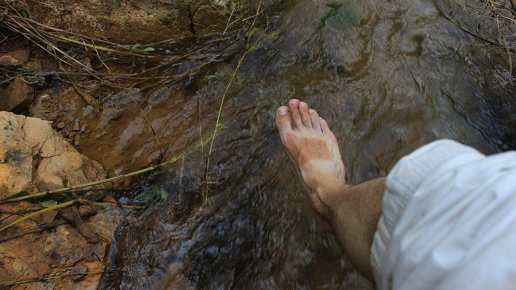 A foot with a clearly visible sandal tan hanging above a stream.