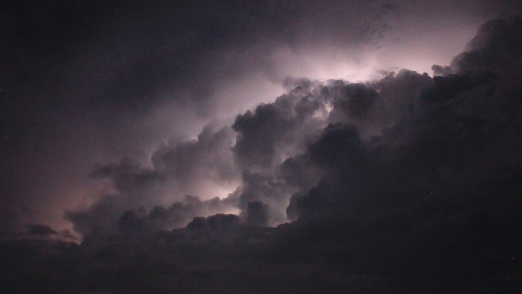 A silent lightning storm with eerie purple light appearing behind dark clouds.