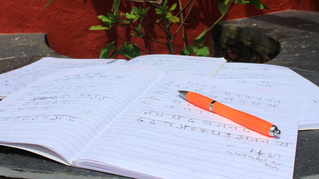 Nepalese letters written on Devanagari script on a school notebook.