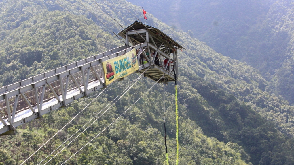 The bungee jump tower in Pokhara rises above a river gorge.