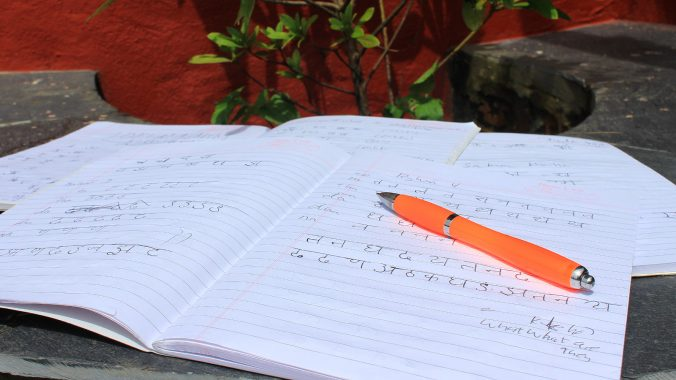 Writing the Nepali language basics. on a notebook.