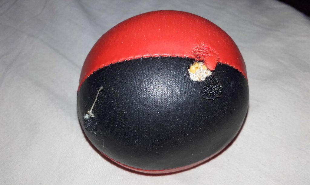 A striped red and black juggling ball with a hole in it and seeds inside.