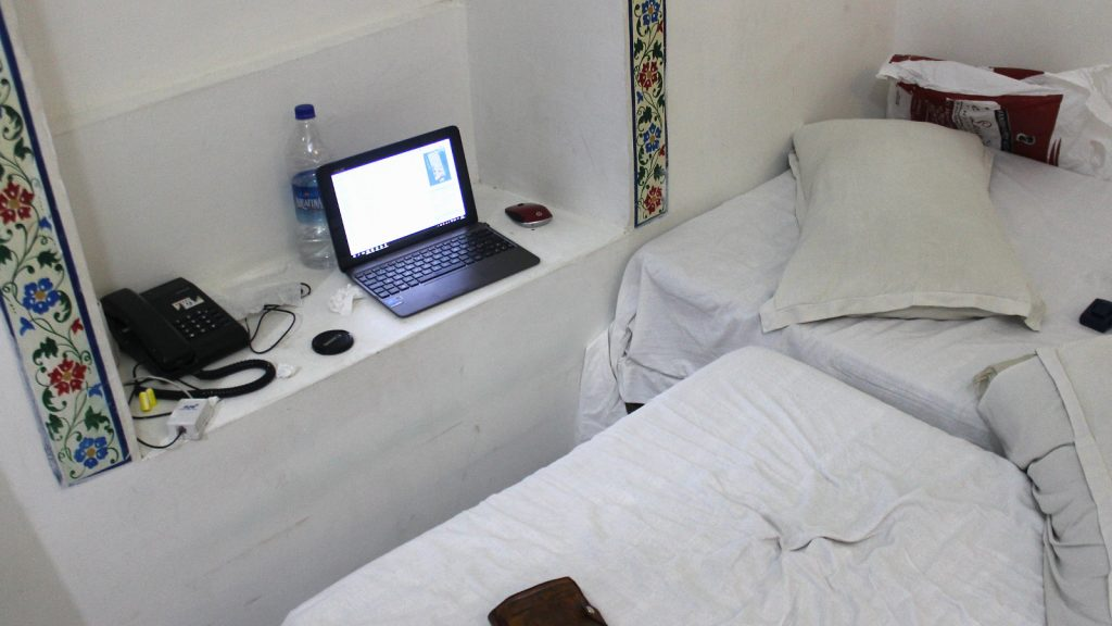 A laptop set on an inset on the wall with bed workings as a chair.