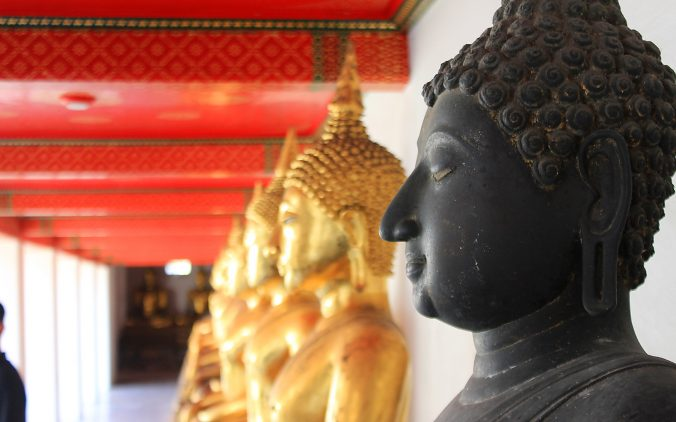 Lifting my travel mod. Gilded Buddha statues from the side in Wat Pho, Bangkok, Thailand.