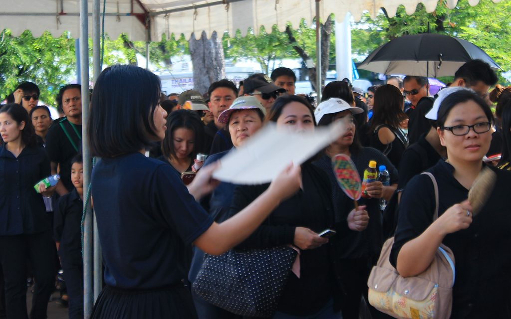 A Thai woman waving a cardboard fan to cool people waiting on a line to enter the Grand Palace in Bangkok, Thailand. Mourners wait to pay their respects for late King Bhumibol.