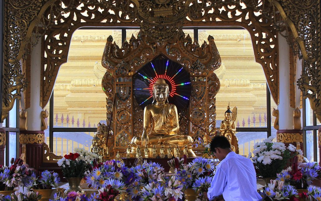 A sitting Buddha statue in Mandalay, Myanmar with a flashing neon sign circle behind his head.