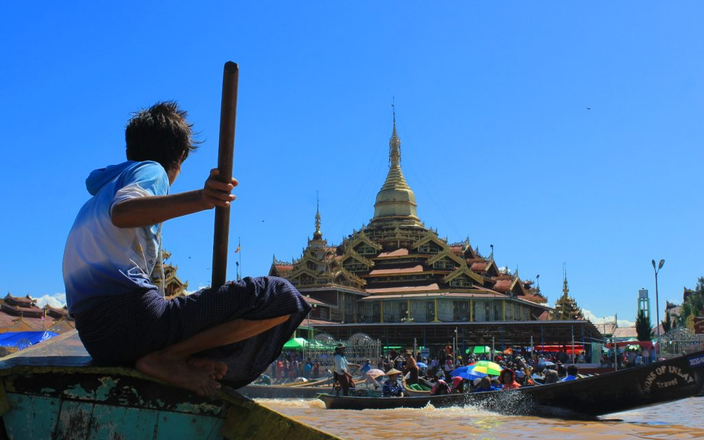 Myanmar pictures. A young boy leading a boat to Hpaung Daw U Pagoda in Inle Lake.