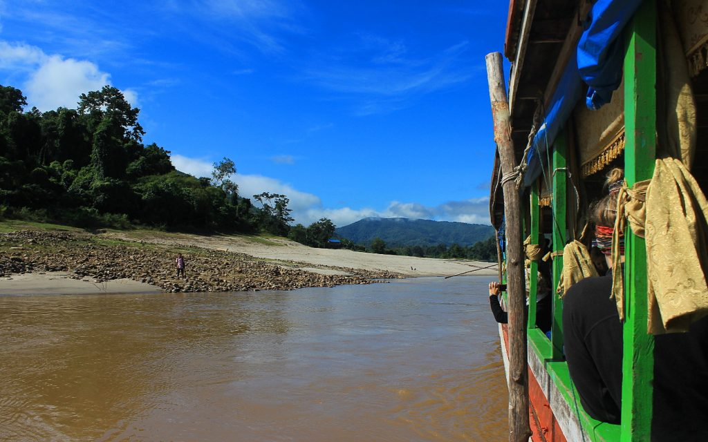 Slow boat to Luang Prabang stopping on a sandy shore with only one man visible on the coast.
